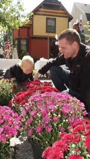 Little Aria and her father Adam smell the mums at R&A Greenhouse and Garden's booth at the festival.